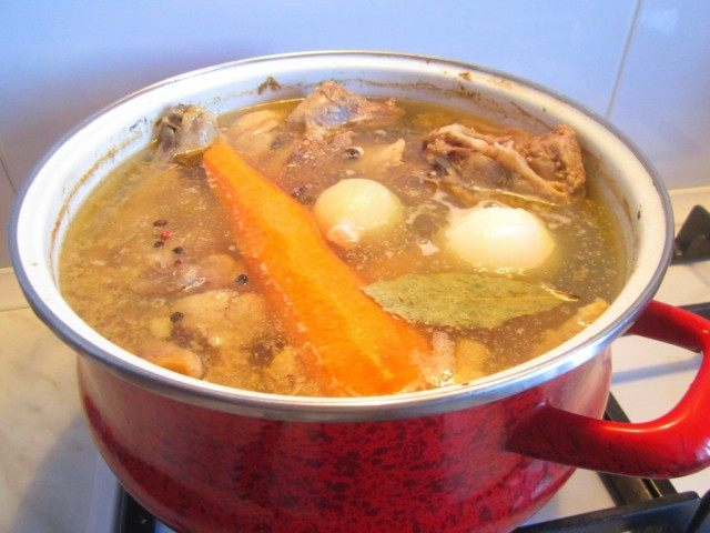 Добавьте в горячий бульон для холодца лук, морковь и лавровый лист