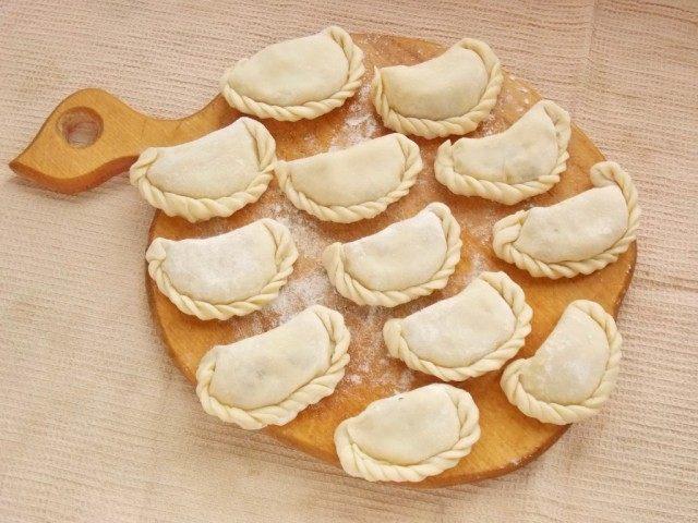 Выложите слепленные вареники с картошкой на доску и присыпьте мукой
