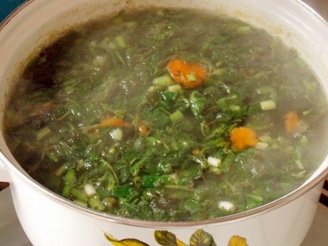 Добавьте крапиву и зелёный лук в бульон и варим несколько минут