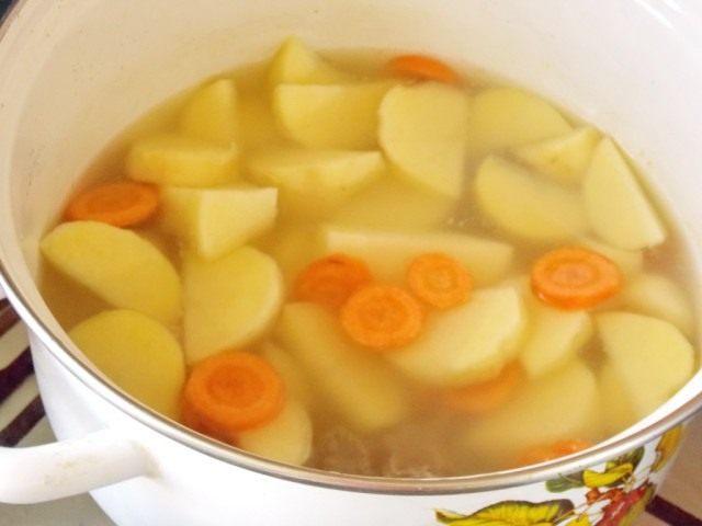 Выкладываем в кастрюлю картофель и морковь и ставим тушиться