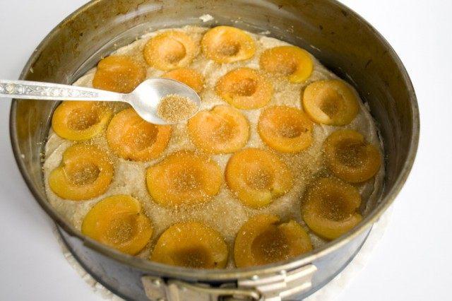Выкладывает тесто в форму для запекания и покрываем абрикосами