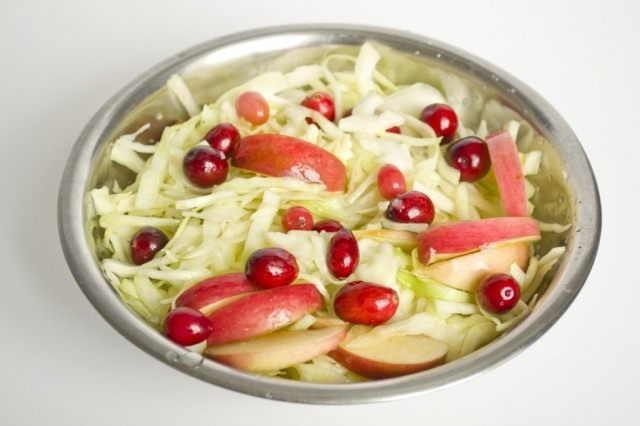 Добавляем в капусту ягоды клюквы и нарезанные яблоки