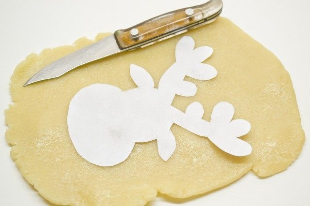 Из песочного теста вырезаем по шаблону печенье и ставим выпекаться