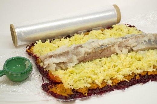 Выкладываем слоями свёклу, морковь и картошку. Затем кладём сельдь