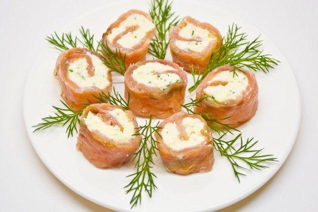 Готовые рулет из красной рыбы домашнего посола с сыром нарезаем перед подачей