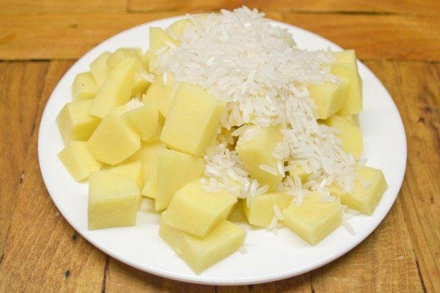 В кастрюлю выкладываем обжаренные овощи, картофель и рис. Варим до готовности риса