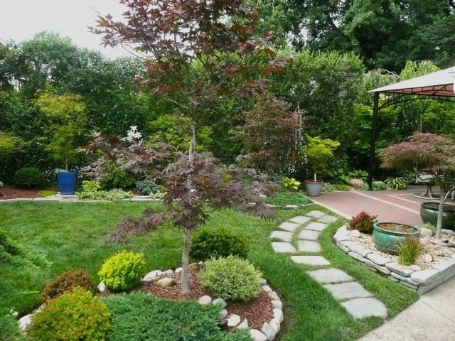 Сад в японском стиле. Использованы: Клён дланевидный 'Emperor I'; низкорослые спиреи; Барбарис тунберга 'Golden Ruby'; Барбарис 'Golden Nugget'; Кипарисовик горохоплодный 'Snow'; можжевельника голубой стелющейся