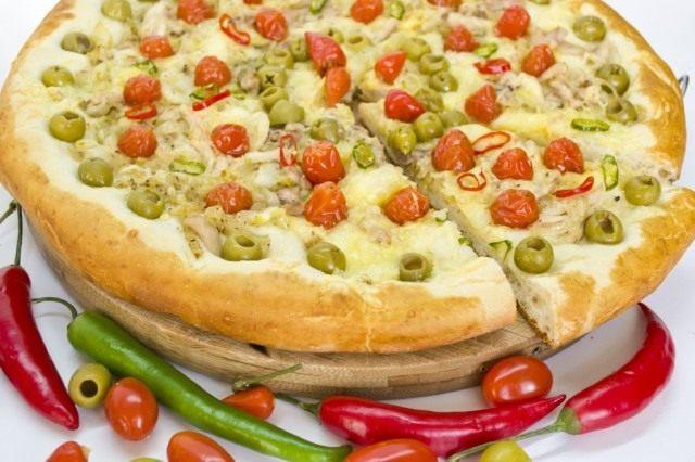 Готовую пиццу с курицей и томатами черри подаем горячей