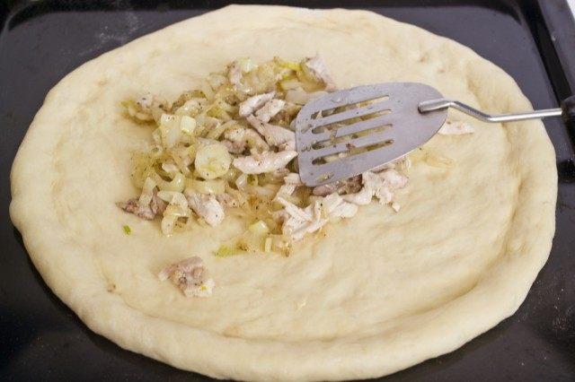 Отваренную курицу и жареный лук приправляем и выкладываем на тесто