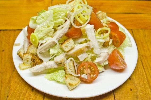 Выкладываем салат Цезарь на тарелку