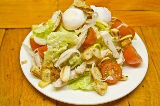 Кладём на верхушку салата перепелиные яйца, посыпаем всё обжаренными орешками
