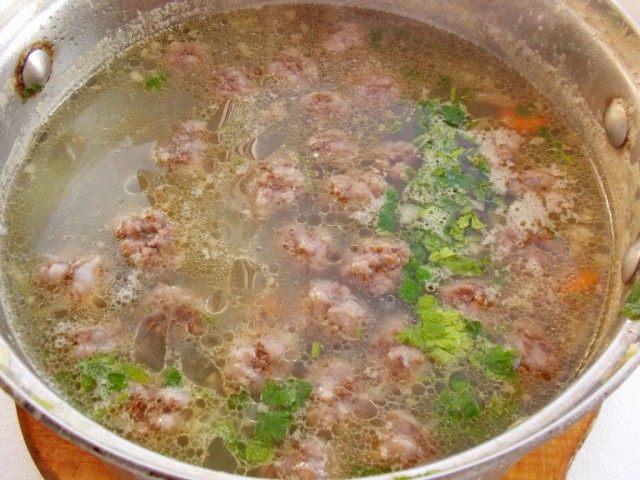 Добавляем в суп лук и фрикадельки. Варим 5-6 минут, добавляем зелень и специи