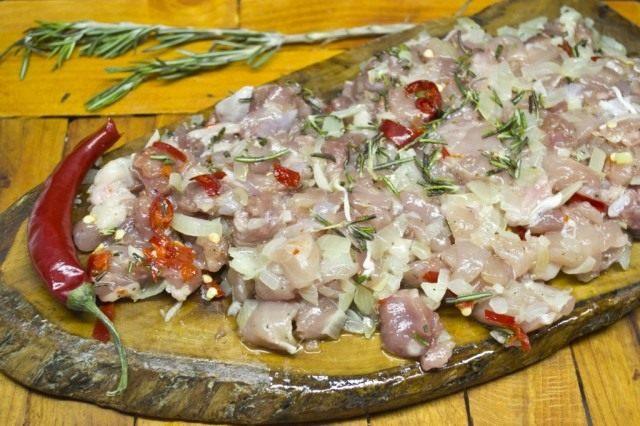 Добавляем мелко нарезанный острый перец и розмарин. Перемешиваем фарш