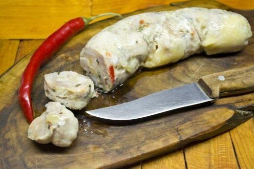 Готовую варёную колбасу из индейки с розмарином и сыром остужаем, снимаем плёнку и подаем, нарезав ломтиками