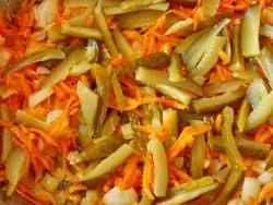 Добавляем к луку и моркови солёные огурцы