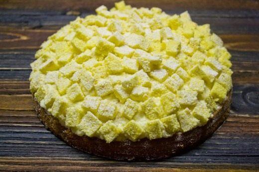 Выкладываем сверху желтые кубики бисквита и присыпаем сахарной пудрой