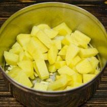 Обжариваем порубленную головку репчатого лука, зубчики чеснока и кубики картофеля