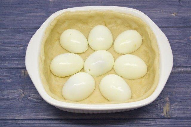 Раскатываем 2/3 теста для основы и выкладываем в форму. Выкладываем отваренные яйца.