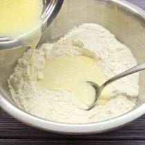 Горячее молоко с маслом выливаем в муку и замешиваем тесто