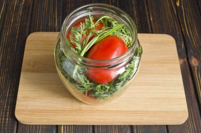 Выкладываем помидоры и морковную ботву в банку и заливаем на несколько минут кипятком
