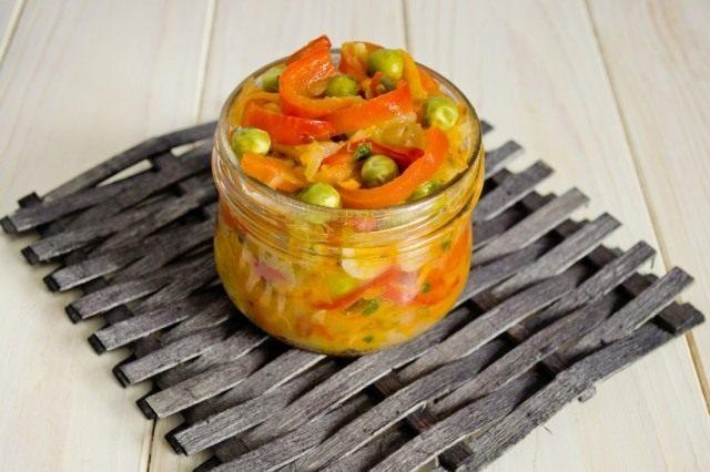 Готовый салат из сладкого перца с цуккини и горошком выкладываем в банки для стерилизации