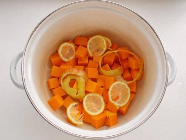 В кастрюлю выкладываем нарезанную тыкву, кожуру яблока и лимон