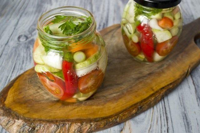 Раскладываем салат по банкам, добавляем зелень петрушки и мяты. Заливаем маринадом