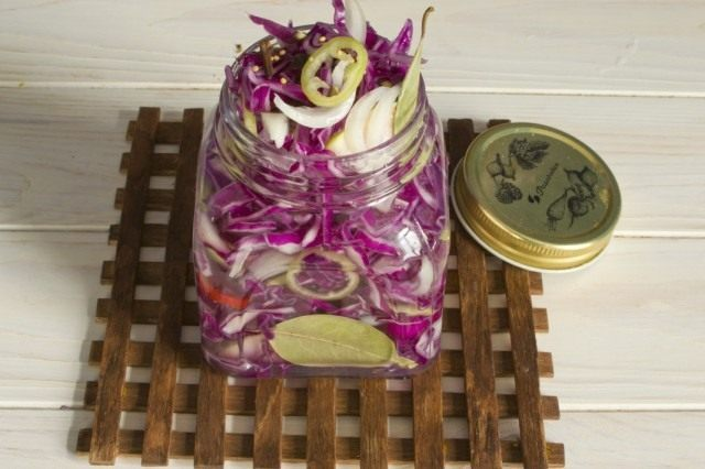 В готовые банки выкладываем купусту и овощи, заливаем маринадом и стерилизуем
