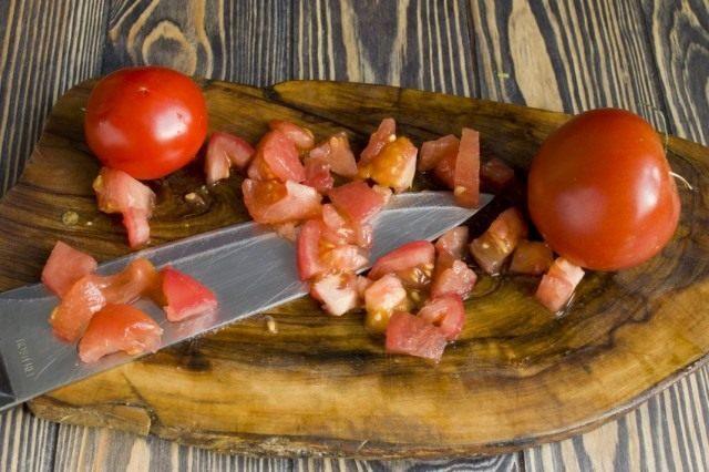 Нарезаем очищенные помидоры и добавляем в рагу