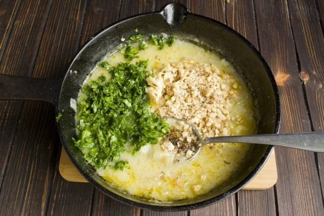 Выкладываем в бульон растёртые грецкий орех и чеснок, нарезанную кинзу и хмели-сунели