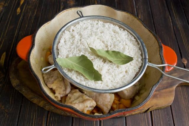 Выкладываем на мясо рис и лавровый лист