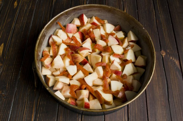 В форму для запекания выкладываем нарезанные яблоки и курагу