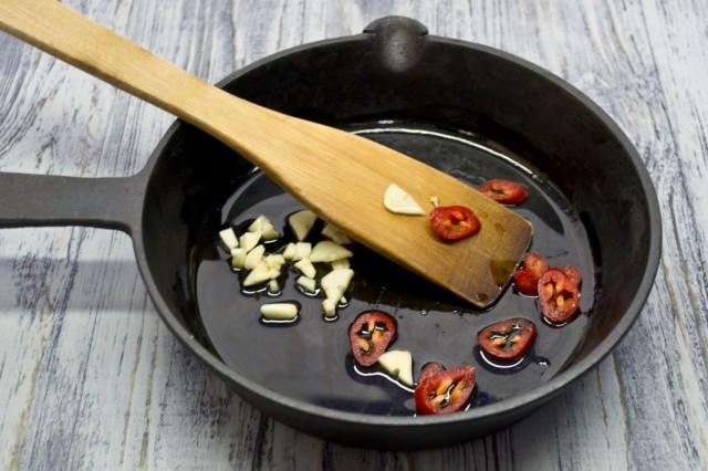 В полученном жире обжариваем чеснок и острый перец