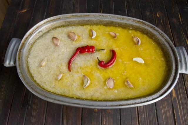 Наливаем горячую воду, солим, выкладываем чеснок и острый перец