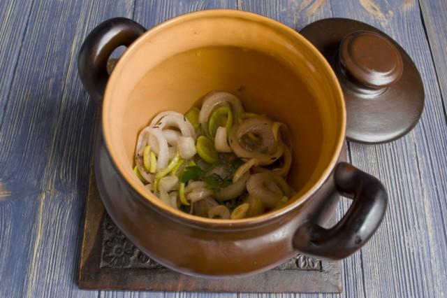 На дно горшочка выкладываем сливочное масло и лук из маринада