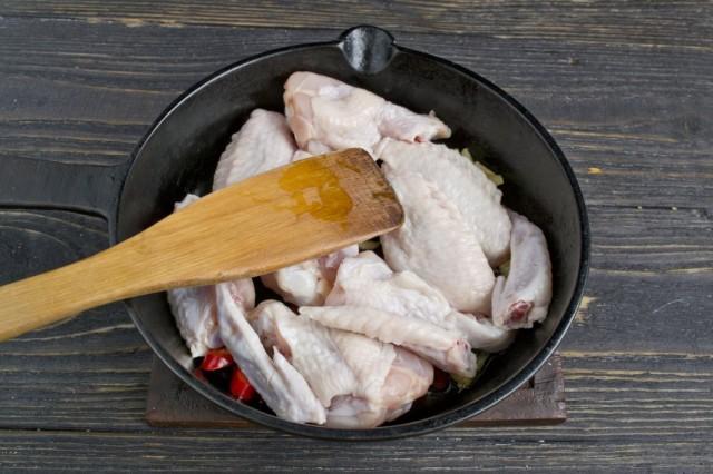 Обжариваем в ароматизированном масле куриные крылышки