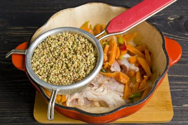 В жаровню с пассерованными овощами выкладываем маринованную курицу и сверху чечевицу