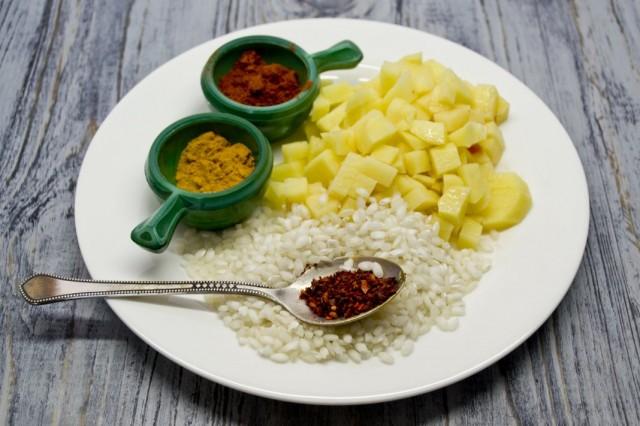 Добавляем в бульон картофель, рис и специи