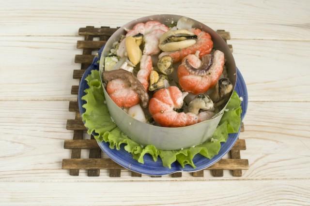 Обжаренные морепродукты выкладываем на салат, поливаем соком