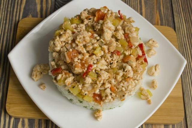 Выкладываем на тарелку рис, а сверху — овощи с мясом