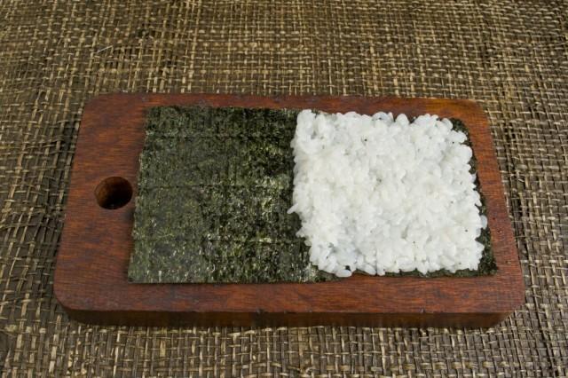 На половину листа нори выкладываем рис и распределяем его