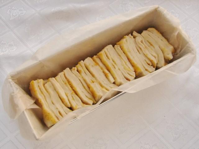 Форму для запекания выстилаем пергаментом и выкладываем в неё нарезанное тесто