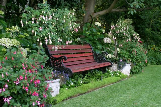 Лавочка возле цветника с садовыми вазонами