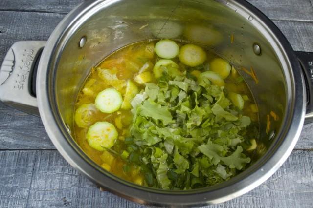 Наливаем в кастрюлю бульон, доводим до кипения и добавляем зелень и салат