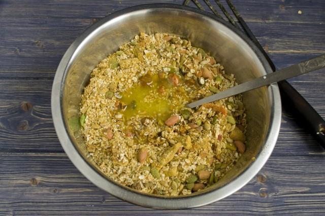 В обжаренные мюсли добавляем растопленный мёд и тщательно перемешиваем