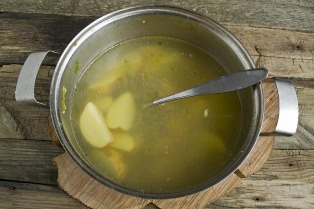 Кладём в бульон очищенный молодой картофель