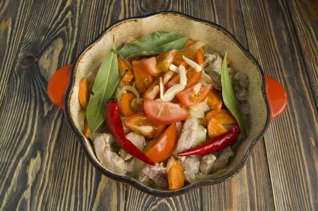 Добавляем перец чили, лавровый лист, чеснок и помидоры