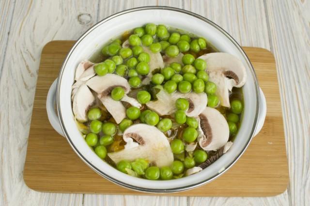 Добавляем зелёный горошек и заливаем процеженным куриным бульоном
