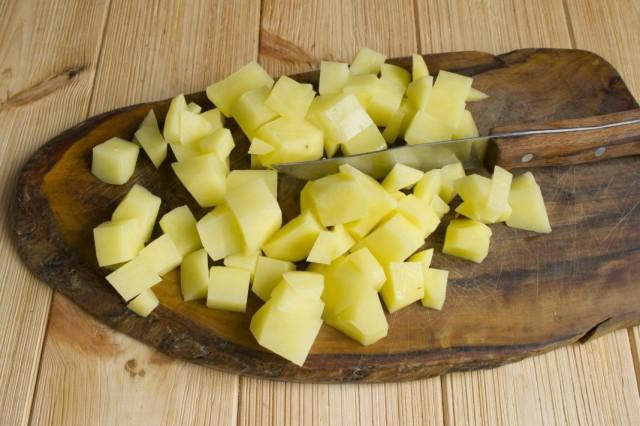 В кастрюлю с бульоном добавляем нарезанный картофель