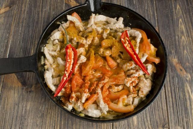 Добавляем в сковороду томатное пюре, специи и острый перец чили